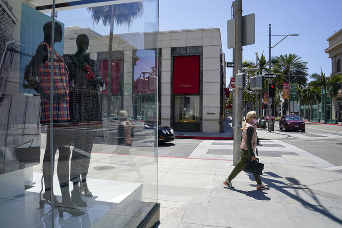 A woman wearing a face mask walks past a window display at Chanel on Rodeo Drive Tuesday, May 19, 2020, in Beverly Hills, Calif. (AP Photo/Ashley Landis)