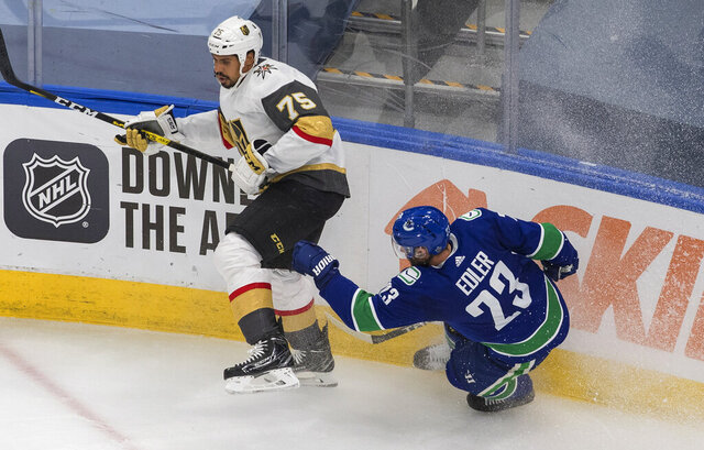 Vegas Golden Knights' Ryan Reaves (75) checks Vancouver Canucks' Alexander Edler (23) during the third period of Game 3 of an NHL hockey second-round playoff series, Saturday, Aug. 29, 2020, in Edmonton, Alberta. (Jason Franson/The Canadian Press via AP)