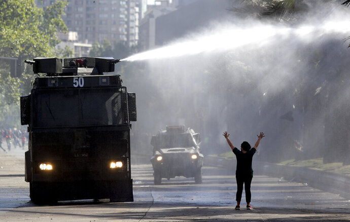 A protester holds her hands up toward a police truck spraying a water canon at students and union members marching in Santiago, Chile, Monday, Oct. 21, 2019. At least 18 people have died in the turmoil that has swept the South American nation, where the unrest began as a protest over a 4-cent increase in subway fares and soon morphed into a larger movement over growing inequality in one of Latin America's wealthiest countries. (AP Photo/Miguel Arenas)