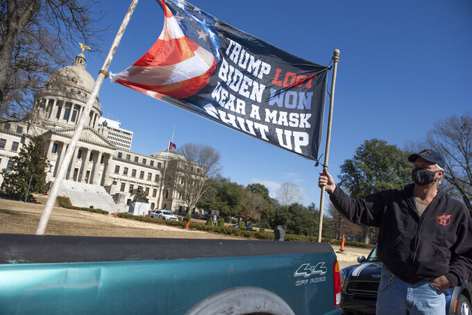"Dale Gibson, of Jackson, Miss., shows off the banner he planned to hold as a counter-protester if a pro-Trump rally materialized Sunday, Jan. 17, 2021. ""But they done ruined my whole Sunday. Now I have to go and get drunk,"" Gibson said. Visibly enhanced security surrounded the Mississippi State Capitol in Jackson, Miss., after FBI warned armed protests had been planned at all 50 state capitols leading up to the inauguration of President-elect Joe Biden. (Barbara Gauntt/The Clarion-Ledger via AP)"