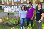 From left, Beth Woolsey, Tai Haden-Moore and AJ Schwanz , who are members of a group called Newberg Equity in Education which is advocating for inclusion and equity in schools, stand in front of a school district office in Newberg, Ore., on Tuesday, Sept. 21, 2021. The Newberg School Board has banned educators from displaying Black Lives Matter and gay pride symbols, prompting a torrent of recriminations and threats to boycott the town and its businesses. (AP Photo/Andrew Selsky)