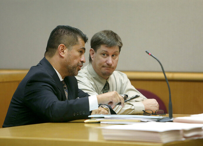 FILE - In an Oct. 19, 2018 file photo, attorney Bryant Camareno talks to his client defendant Michael Drejka during a pretrial hearing, at the Pinellas County Criminal Justice Center in Clearwater, Fla. The manslaughter trial of Drejka, accused of fatally shooting an unarmed black man in a Florida parking lot, will focus on the state's controversial