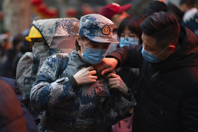 In this photo taken Jan 24, 2020 and released by Xinhua News Agency, a military medic from the Air Force Medical University prepares to leave for Wuhan from Xi'an, capital of northwestern China's Shaanxi Province. The Chinese military dispatched medical staff, some with experience in past outbreaks including SARS and Ebola, to help treat the many patients hospitalized with viral pneumonia, Xinhua reported. (Zhang Haopeng/Xinhua via AP)