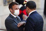 French President Emmanuel Macron, left, greets Libyan Prime Minister Abdulhamid Dbeibeh before their meeting at the Elysee Palace, in Paris, Tuesday, June 1, 2021. (AP Photo/Francois Mori)