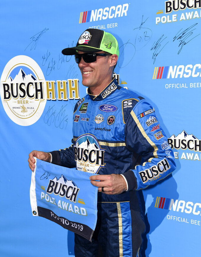 Kevin Harvick poses with the pole award after qualifying for Sunday's NASCAR Cup Series auto race, Saturday, July 27, 2019, in Long Pond, Pa. (AP Photo/Derik Hamilton)