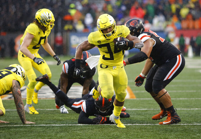 Oregon running back C.J. Verdell (34) breaks through the Oregon State defensive line for a touchdown during the second half of an NCAA college football game in Corvallis, Ore., Friday, Nov. 23, 2018. Oregon won 55-15. (AP Photo/Timothy J. Gonzalez)