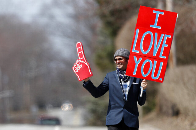 Sam Mawhinney does his best to bring a moments of joy to motorists as spreads his message of love while walking in Cape Elizabeth, Maine, Wednesday, April 8, 2020. Officials announced Wednesday that Maine now has more than 500 confirmed cases of coronavirus. (AP Photo/Robert F. Bukaty)