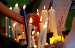 A women's rights activist places a candle beside a poster during a candle light vigil to pay tribute to Noor Mukadam, who was recently beheaded, and other domestic violence victims in Islamabad, Pakistan, Sunday, July 25, 2021. The killing of Mukadam in an upscale neighborhood of Pakistan's capital has shone a spotlight on the relentless violence against women in the country. Rights activists say such gender-based assaults are on the rise as Pakistan barrels toward greater religious extremism. (AP Photo/Anjum Naveed)
