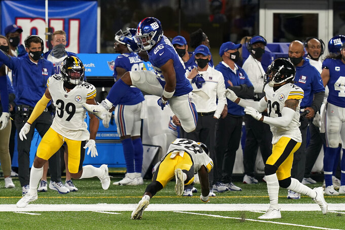 New York Giants running back Saquon Barkley (26) leaps over Pittsburgh Steelers cornerback Mike Hilton (28) during the second quarter of an NFL football game Monday, Sept. 14, 2020, in East Rutherford, N.J. (AP Photo/Seth Wenig)