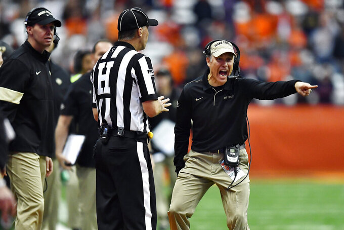 Wake Forest head coach Dave Clawson, right, speaks to an official during the second half of an NCAA college football game against Syracuse in Syracuse, N.Y., Saturday, Nov. 30, 2019. Syracuse beat Wake Forest 39-30 in overtime. (AP Photo/Adrian Kraus)