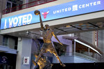 The Michael Jordan statue stands in front of an I Voted banner on Election Day, Tuesday, Nov. 3, 2020, in the atrium of the United Center, transformed for the first time into a super voting site in Chicago. (AP Photo/Charles Rex Arbogast)