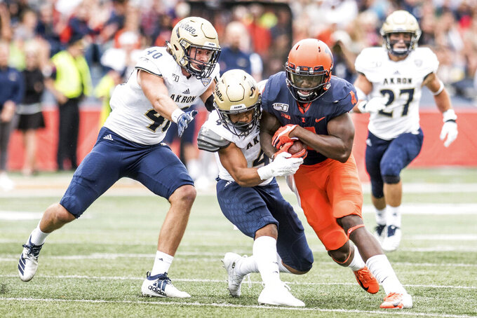 Illinois's Ricky Smalling (4) is tackled by Akron's John Lasso, left, and Dylan Meeks after making a catch in the first half of a NCAA college football game, Saturday, Aug. 31, 2019, in Champaign, Ill. (AP Photo/Holly Hart)