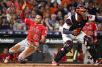 Los Angeles Angels' Michael Hermosillo (21) slides past Houston Astros catcher Martin Maldonado to score a run on Andrelton Simmons' single during the sixth inning of a baseball game, Saturday, Sept. 21, 2019, in Houston. (AP Photo/Eric Christian Smith)