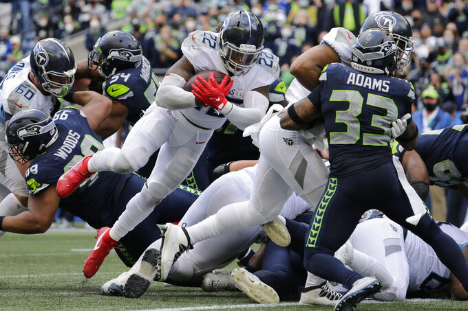 Tennessee Titans running back Derrick Henry (22) scores a touchdown against the Seattle Seahawks during the second half of an NFL football game, Sunday, Sept. 19, 2021, in Seattle. The extra point was good and the score tied the game at 30-30. (AP Photo/John Froschauer)