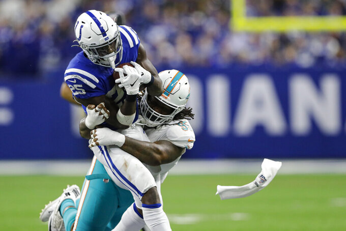 Indianapolis Colts running back Marlon Mack (25) is tackled by Miami Dolphins defensive end Taco Charlton (96) during the second half of an NFL football game in Indianapolis, Sunday, Nov. 10, 2019. (AP Photo/Darron Cummings)