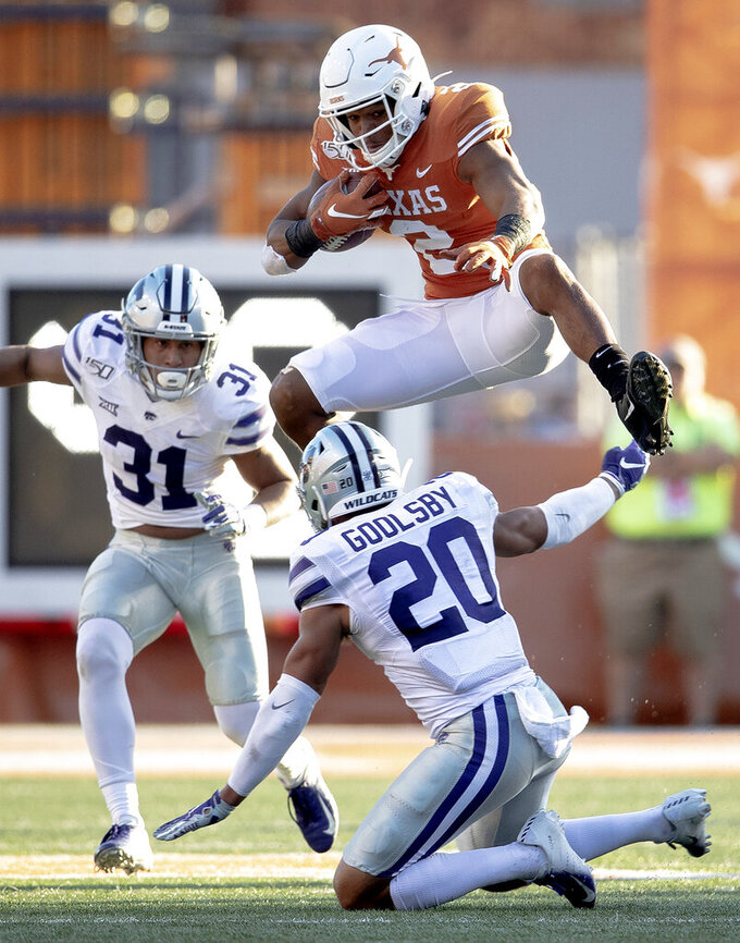 Texas running back Roschon Johnson (2) hurdles Kansas State defensive back Denzel Goolsby (20) during an NCAA college football game Saturday, Nov. 9, 2019, in Austin, Texas. (Nick Wagner/Austin American-Statesman via AP)