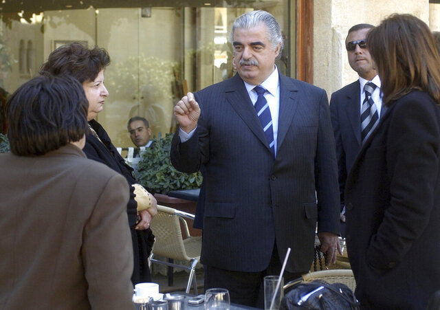 FILE - In this Feb. 14, 2005 file photo, former Lebanese Prime Minister Rafik Hariri, center, speaks to people outside the Lebanese Parliament minutes before an explosion killed him and 22 others, in Beirut, Lebanon. More than 15 years after the truck bomb assassination of Hariri in Beirut, a U.N.-backed tribunal in the Netherlands is announcing verdicts this week in the trial of four members of the militant group Hezbollah allegedly involved in the killing. (AP Photo, File)