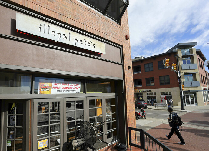FILE - In this Oct. 23, 2014, file photo, a man walks past an Illegal Pete's restaurant in Boulder, Colo. Delaware officials won't allow popular Colorado-based restaurant chain Illegal Pete's to convert to a Delaware limited liability company because the company's name has