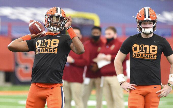 Syracuse quarterback JaCobian Morgan, left, warms up before an NCAA college football game against Boston College, Saturday, Nov. 7, 2020, at the Carrier Dome in Syracuse, N.Y. (Dennis Nett/The Post-Standard via AP)