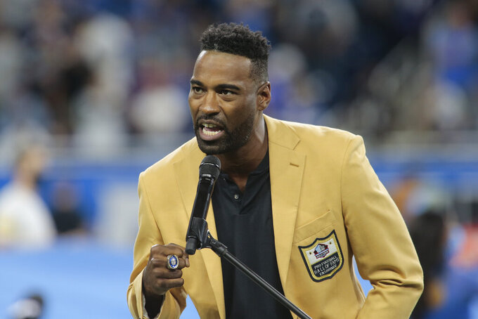Former Detroit Lions wide receiver Calvin Johnson speaks after being presented his Hall of Fame ring during halftime of an NFL football game against the Baltimore Ravens in Detroit, Sunday, Sept. 26, 2021. (AP Photo/Tony Ding)