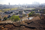 FILE - In this Dec. 14, 2017, file photo, Los Angeles Fire Department Arson Counter-Terrorism investigators check a burned-out homeless camp after a brush fire erupted in the hills in Elysian Park near downtown Los Angeles. Authorities say fires linked to homeless tents and camps are raising concern in Los Angeles, where they have claimed seven lives and caused tens of millions of dollars in damage to nearby businesses. The Los Angeles Times says the Fire Department handled 24 such fires a day in the first quarter of this year. (AP Photo/Damian Dovarganes, File)