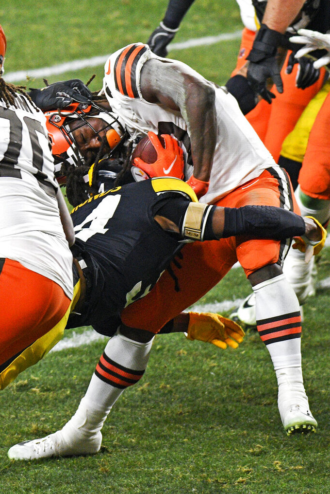 Cleveland Browns running back Kareem Hunt (27) is tackled by Pittsburgh Steelers strong safety Terrell Edmunds (34) during the second half of an NFL wild-card playoff football game in Pittsburgh, late Sunday, Jan. 10, 2021. (AP Photo/Don Wright)