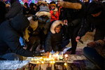 Mourners place candles and photographs outside the Alberta Legislature Building in Edmonton, Alberta, Wednesday, Jan. 8, 2020, during a vigil for those killed after a Ukrainian passenger jet crashed, killing at least 63 Canadians, just minutes after taking off from Iran's capital. (Codie McLachlan/The Canadian Press via AP)