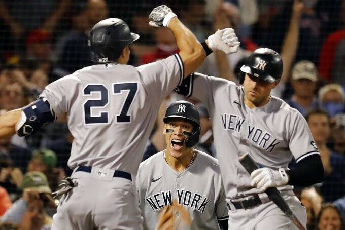 New York Yankees' Giancarlo Stanton (27) celebrates his two-run home run with Joey Gallo, right, that also drove in Aaron Judge, center, during the eighth inning of a baseball game, Sunday, Sept. 26, 2021, in Boston. (AP Photo/Michael Dwyer)
