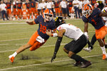 Illinois quarterback Brandon Peters makes a cut as Maryland defensive back Nick Cross comes up to make a tackle during the first half of an NCAA college football game Friday, Sept. 17, 2021, in Champaign, Ill. (AP Photo/Charles Rex Arbogast)