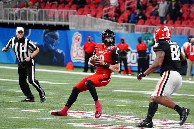 Cincinnati quarterback Desmond Ridder (9) prepares to throw a touchdown pass against Georgia during the first half of the Peach Bowl NCAA college football game, Friday, Jan. 1, 2021, in Atlanta. (AP Photo/Brynn Anderson)