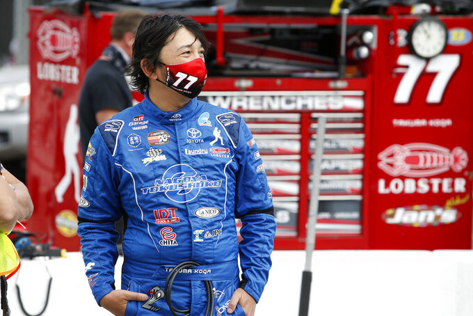 Takuma Koga, of Japan, looks on from pit road prior to an ARCA Series auto race at Phoenix Raceway, Saturday, Nov. 7, 2020, in Avondale, Ariz. (AP Photo/Ralph Freso)