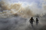 Firefighters walk through a cloud of smoke as winds fuel the Easy Fire Wednesday, Oct. 30, 2019, in Simi Valley, Calif. Fire officials say they're investigating the cause of the fire. (AP Photo/Marcio Jose Sanchez)