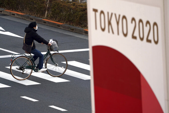 FILE - In this Jan. 21, 2021, file photo, a man wearing a protective mask to help curb the spread of the coronavirus rides a bicycle near a banner of the Tokyo 2020 Olympics in Tokyo. IOC officials say the Tokyo Olympics will open on July 23 and almost nothing now can stop the games from going forward. (AP Photo/Eugene Hoshiko, File)