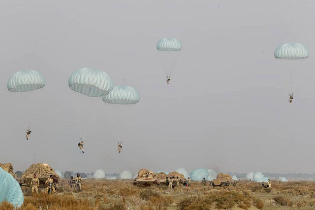 In this photo released on Tuesday, Jan. 19, 2021, by the Iranian Army, shows paratroopers parachuting during a military drill. Iran's military kicked off a ground forces drill on Tuesday along the coast of the Gulf of Oman, state TV reported, the latest in a series of snap exercises that the country is holding amid escalating tensions over its nuclear program and Washington's pressure campaign against Tehran. (Iranian Army via AP)