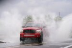 A vehicle sprays water in the air while driving through standing water as heavy rains caused flooding, Friday, July 23, 2021, in Phoenix. (AP Photo/Ross D. Franklin)