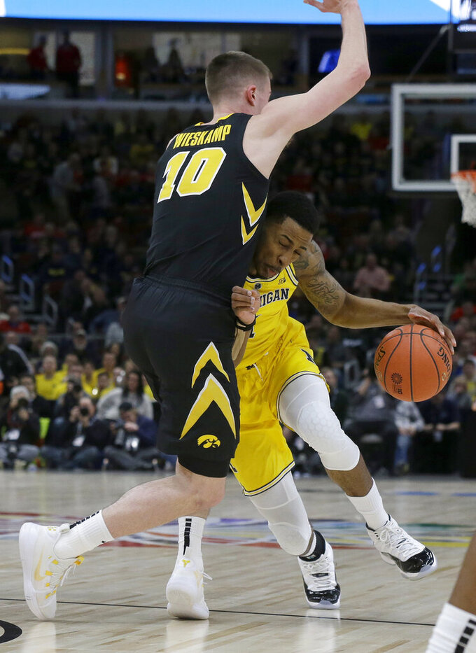 Michigan's Charles Matthews drives against Iowa's Joe Wieskamp (10) during the first half of an NCAA college basketball game in the quarterfinals of the Big Ten Conference tournament, Friday, March 15, 2019, in Chicago. (AP Photo/Kiichiro Sato)
