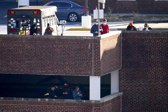 Fans hang out on parking structure to try to catch a glimpse of the second half of an NCAA college football game between Maryland and Rutgers, Saturday, Dec. 12, 2020, in College Park, Md. Rutgers won 27-24 in overtime. (AP Photo/Julio Cortez)