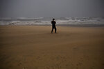 A woman takes photos at the beach during a storm in Barcelona, Spain, Tuesday, Jan. 21, 2020. A winter storm lashed much of Spain for a third day Tuesday, leaving 200,000 people without electricity, schools closed and roads blocked by snow as it killed four people. Massive waves and gale-force winds smashed into seafront towns, damaging many shops and restaurants. (AP Photo/Emilio Morenatti)