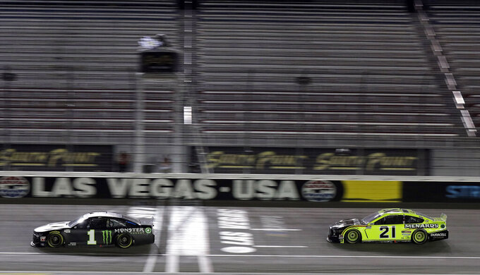 Kurt Busch (1) takes the checkered flag to win a NASCAR Cup Series auto race Sunday, Sept. 27, 2020, in Las Vegas. (AP Photo/Isaac Brekken)
