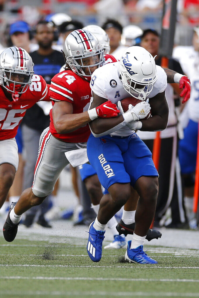 Ohio State defensive back Ronnie Hickman, front left, tackles Tulsa running back Deneric Prince, right, during the second half of an NCAA college football game Saturday, Sept. 18, 2021, in Columbus, Ohio. (AP Photo/Jay LaPrete)