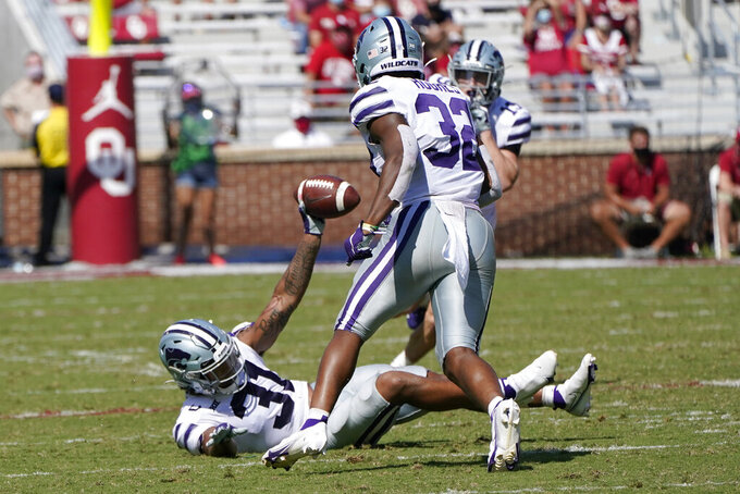 Kansas State defensive back Jahron McPherson (31) celebrates with teammate Justin Hughes (32) after intercepting a pass in the second half of an NCAA college football game against Oklahoma, Saturday, Sept. 26, 2020, in Norman, Okla. (AP Photo/Sue Ogrocki).