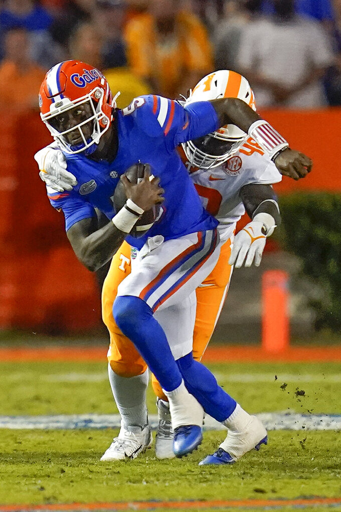Florida quarterback Emory Jones, left, is caught by Tennessee defensive lineman Ja'Quain Blakely during the first half of an NCAA college football game, Saturday, Sept. 25, 2021, in Gainesville, Fla. (AP Photo/John Raoux)