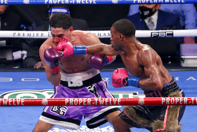 Danny Garcia, left, is hit by Errol Spence Jr. during the WBC IBF welterweight championship boxing bout in Arlington, Texas, Saturday, Dec. 5, 2020. (AP Photo/Brandon Wade)