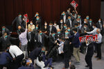Pro-establishment politician, Starry Lee, speaks as pan-democratic legislators scuffle with security guards and pro-China legislators during a Legislative Council's House Committee meeting, in Hong Kong, Friday, May 8, 2020. Scuffles also broke out when Lee called the meeting to order, with pro-democracy lawmakers rushing the table as security shoved back. Security guards physically carried out pro-democracy lawmakers Chu Hoi Dick and Ray Chan, who were ordered to leave due to disorderly conduct. (AP Photo/Kin Cheung)