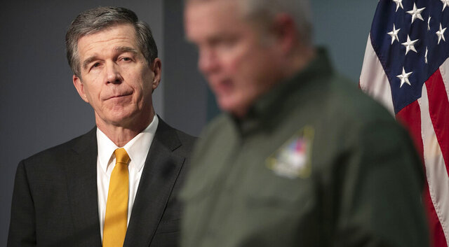 North Carolina Governor Roy Cooper listens to Mike Sprayberry, Director of Emergency Management as he fields questions about FEMA aid during a press briefing on the COVID-19 virus on Wednesday, April 8, 2020, in Raleigh, N.C. (Robert Willett/The News & Observer via AP)
