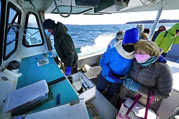 Nurses Kathy Cheney, wearing hat, and Maureen Giffen huddle on a wet and windy ride aboard a lobster boat on the way to set up a COVID-19 vaccination clinic, Friday, March 19, 2021, on Great Cranberry Island, Maine. Getting the vaccine to the world's farthest corners means delivering it by boat to Maine's islands, traveling by snowmobile to villages in Alaska and navigating complex waterways in Brazil's Amazon. (AP Photo/Robert F. Bukaty)