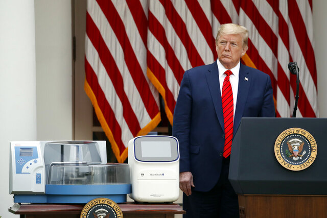 President Donald Trump listens during a briefing about the coronavirus in the Rose Garden of the White House, Monday, May 11, 2020, in Washington. In the foreground are testing machines manufactured by Thermo Fisher Scientific. (AP Photo/Alex Brandon)