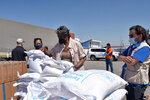 FILE - In this June 3, 2021 handout file photo provided by the US Embassy in Turkey, Linda Thomas-Greenfield, U.S. Ambassador to the United Nations, examines aid materials at the Bab al-Hawa border crossing between Turkey and Syria. Millions of Syrians risk losing access to lifesaving aid, including food and COVID-19 vaccines if Russia gets its way at the Security Council by blocking the use of the last remaining cross-border aid corridor into northwestern Syria, an international rights group said Thursday, June 10. (US Embassy in Turkey via AP)