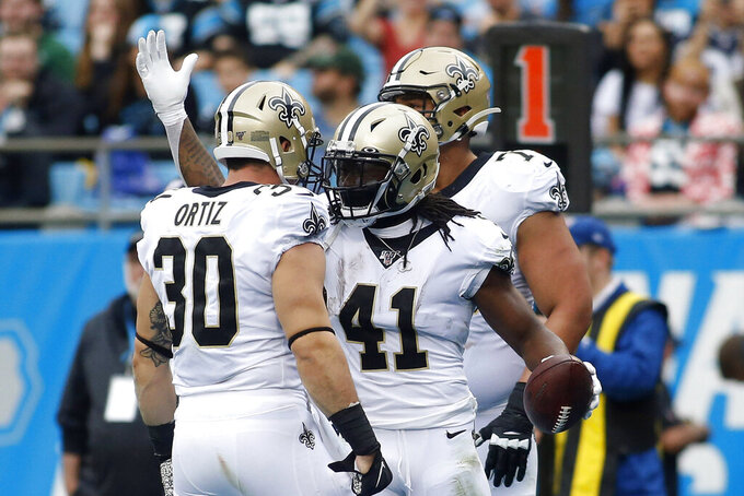 New Orleans Saints running back Alvin Kamara (41) and fullback Ricky Ortiz (30) celebrate Kamara's touchdown against the Carolina Panthers during the first half of an NFL football game in Charlotte, N.C., Sunday, Dec. 29, 2019. (AP Photo/Brian Blanco)