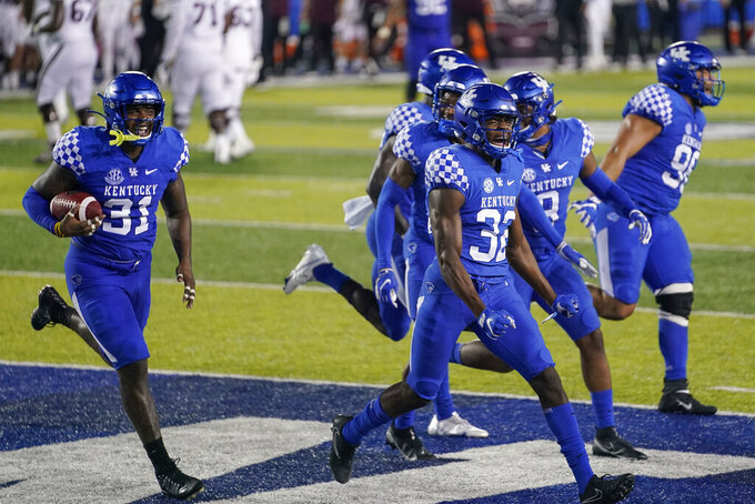 Kentucky wide receiver Darren Edmond (31) celebrates with teammates after he intercepted a Mississippi State pass in end zone during the second half of an NCAA college football game, Saturday, Oct. 10, 2020, in Lexington, Ky. (AP Photo/Bryan Woolston)